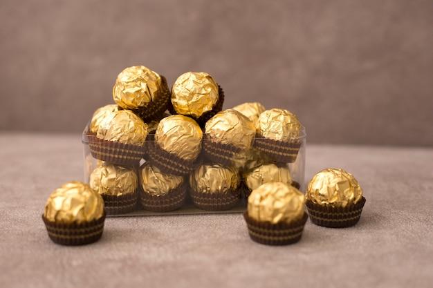 Petite boîte de bonbons au chocolat en feuille d'or se dresse sur un fond brun