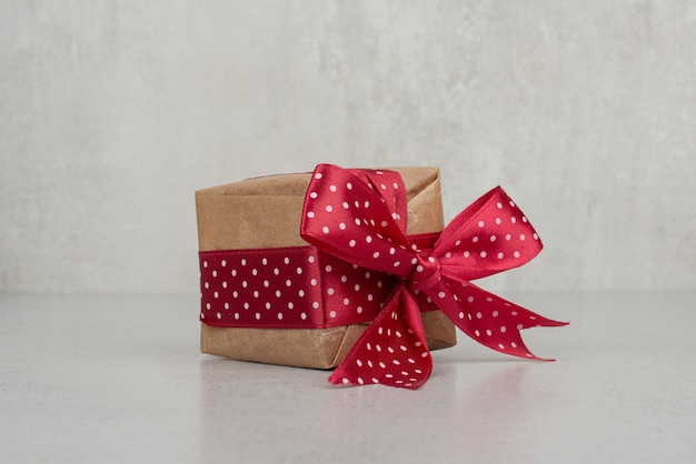 Une petite boîte cadeau avec un arc rouge sur un mur blanc.