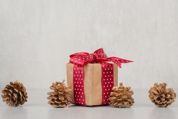 Une petite boîte cadeau avec un arc rouge et de nombreuses pommes de pin sur fond blanc