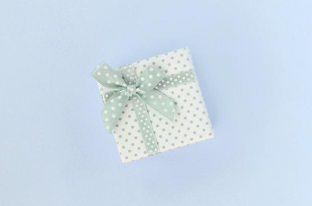 Petite boîte cadeau blanche avec ruban située sur violet