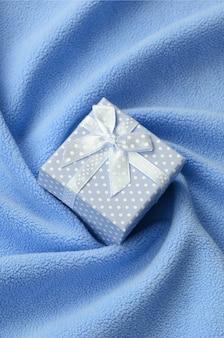 Une petite boîte cadeau en bleu avec un petit noeud repose sur une couverture de douce