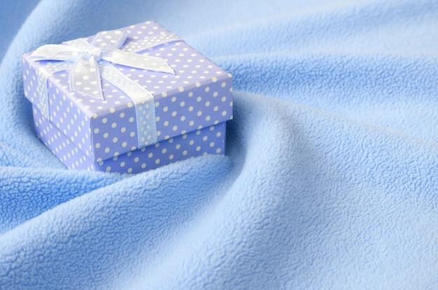 Une petite boîte-cadeau bleue avec un petit noeud repose sur une couverture