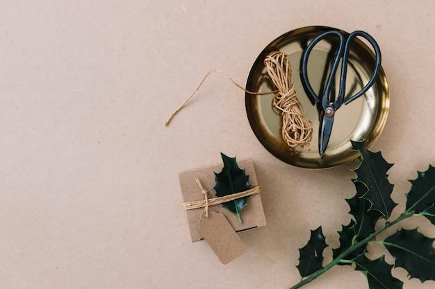 Petite boîte-cadeau avec un dépliant vert noué sur une table marron