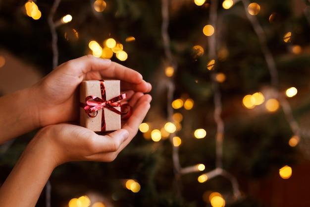 Petite boîte-cadeau de noël avec un arc rouge dans les mains des enfants sur un fond d'éclairage