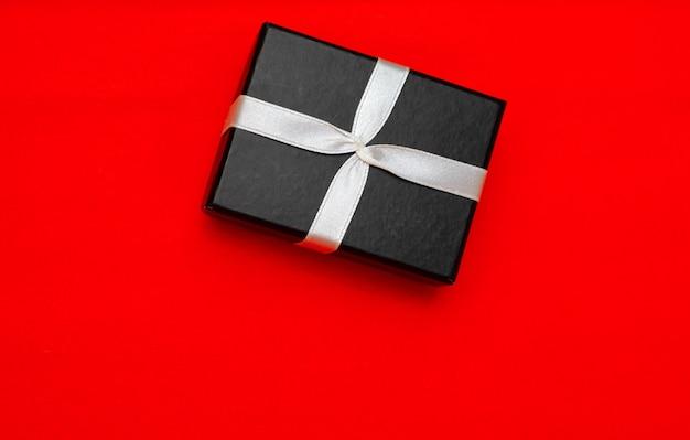Petite boîte cadeau noire rectangulaire sur fond rouge