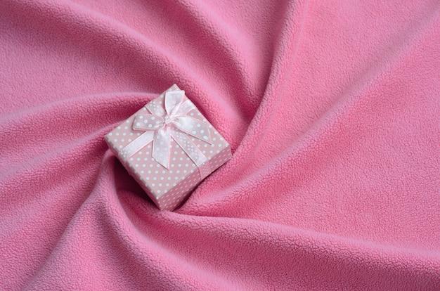 Une petite boîte-cadeau rose avec un petit noeud repose sur une couverture en molleton doux et velu rose pâle