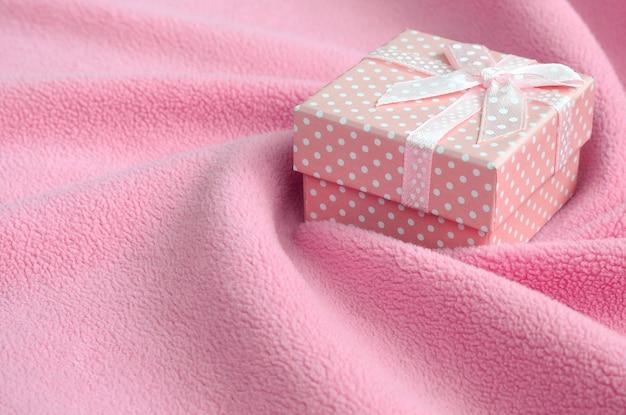 Une petite boîte-cadeau rose avec un petit noeud repose sur une couverture en polaire doux et velu rose pâle avec de nombreux plis en relief.