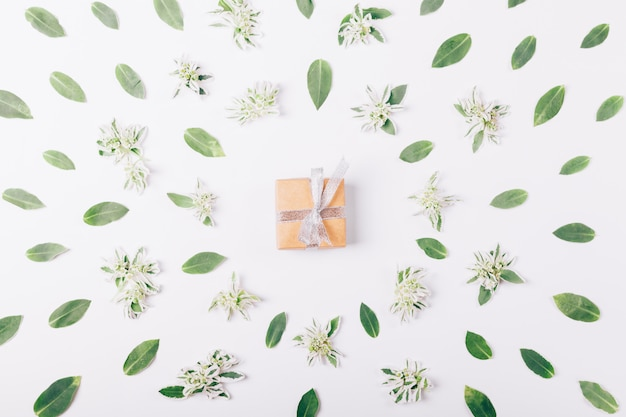 Petite boîte avec un cadeau et un ruban sur une table blanche