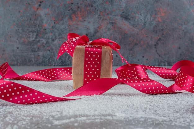 Petite boîte-cadeau et rubans à pois sur la poudre de noix de coco sur la surface en marbre