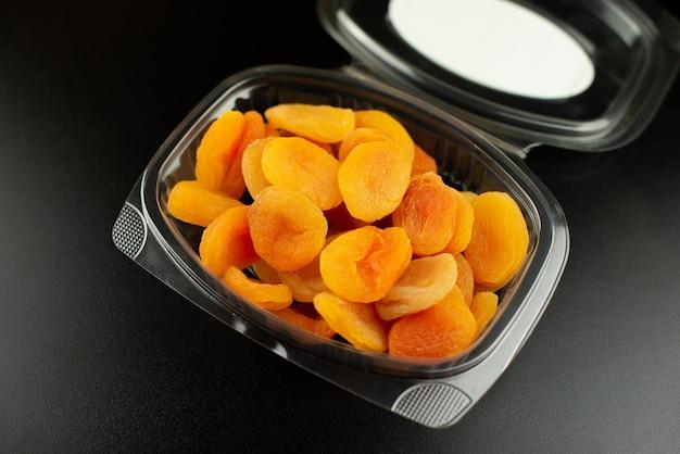 Petite boîte en plastique avec abricot séché sur fond noir.