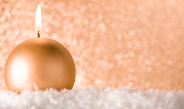 Une petite bougie dorée sur un or brillant.