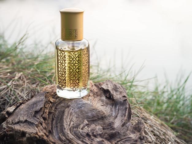 Petite bouteille d'huile d'agarwood parfumée sur un tronc