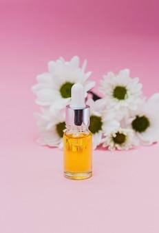 Petite bouteille d'huile cosmétique pour cuticules avec compte-gouttes de fleurs sur fond rose