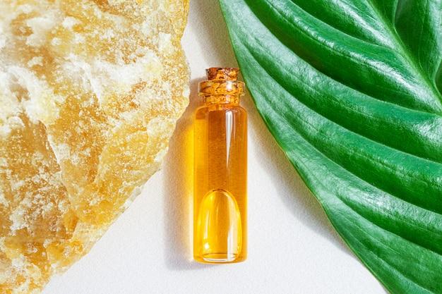Une petite bouteille d'huile essentielle naturelle se situe entre la belle pierre et la feuille de plante fraîche. concept d'essences naturelles, cosmétiques bio, aromathérapie, spa. mise à plat.