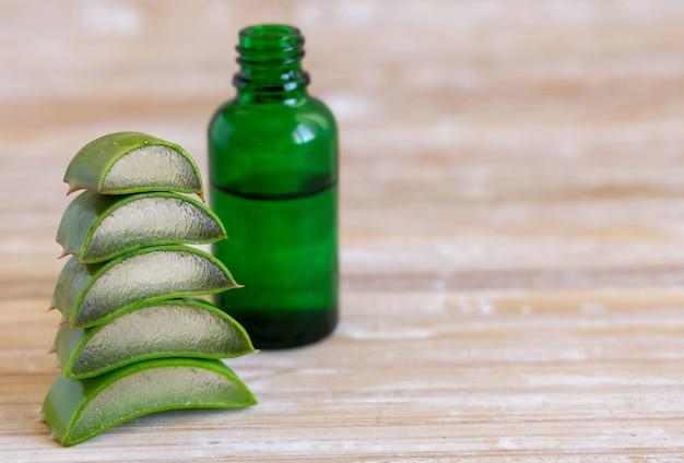 Une petite bouteille verte avec un compte-gouttes et couper les feuilles d'aloe vera close up