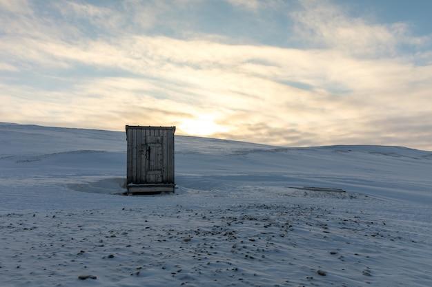 Petite cabane en bois au milieu du paysage arctique en hiver
