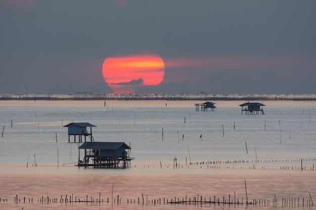 Petite cabane dans la baie de bang taboon avec le grand soleil rouge, au sud de la thaïlande dans la lumière du matin