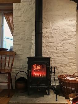 Petite cheminée noire dans la maison murs blancs feu ouvert