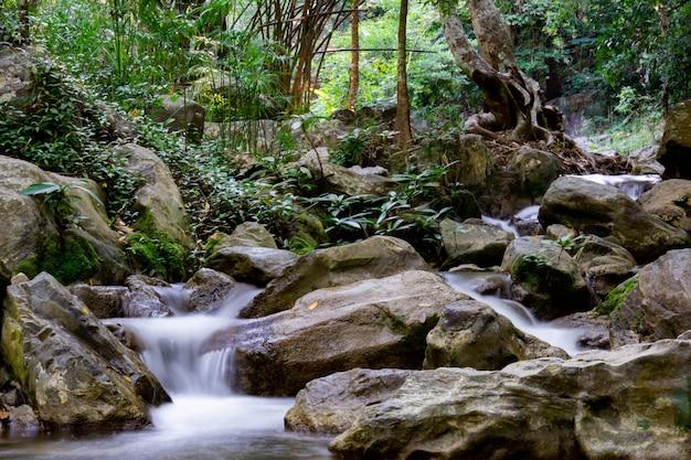 Petite chute d'eau en thaïlande. un petit ruisseau entouré de rochers.