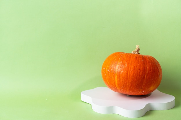 Petite citrouille orange sur fond vert avec espace de copie. célébration de concept d'halloween ou de thanksgiving. podium de cosmétiques pour halloween. automne nature morte.