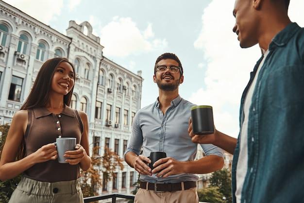 Petite conversation de jeunes collègues positifs en tenue décontractée tenant des tasses et discutant de quelque chose tout en