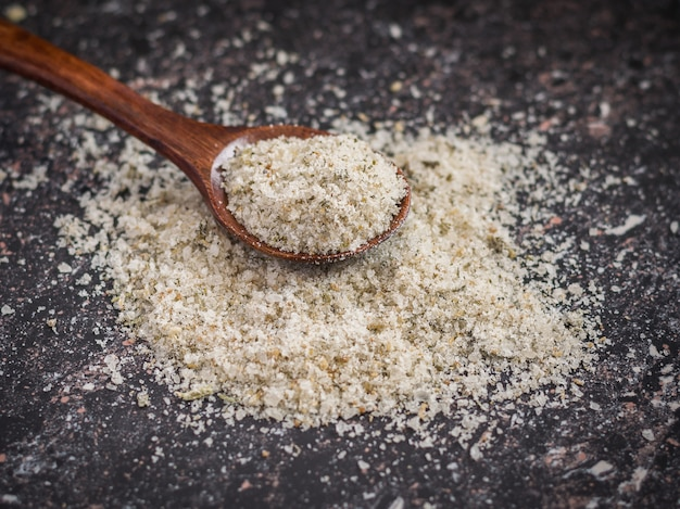 Petite cuillère brune sur un tas de sel avec des herbes sur la table en pierre.