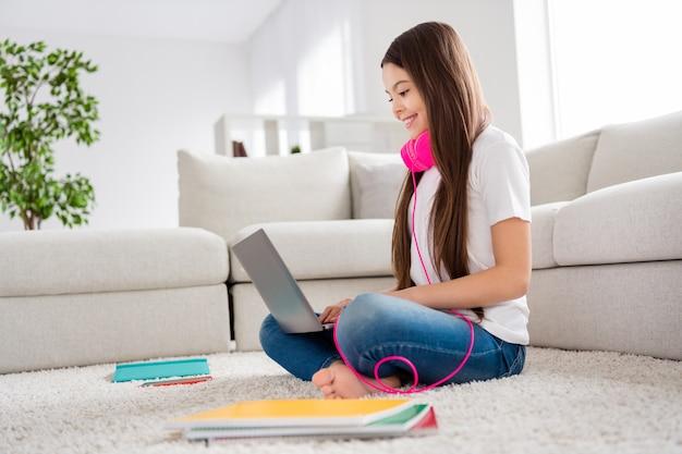 Petite dame rêveuse porter des écouteurs se détendre tapis assis avec ordinateur portable sur les genoux