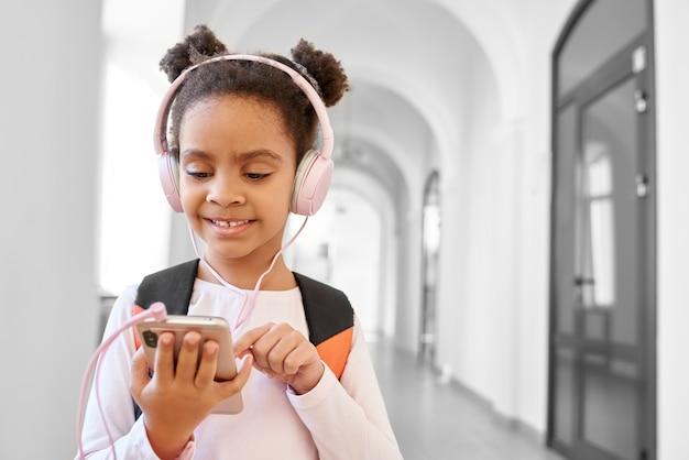 Petite écolière africaine utilisant un téléphone d'appel et écoutant de la musique avec des écouteurs roses.