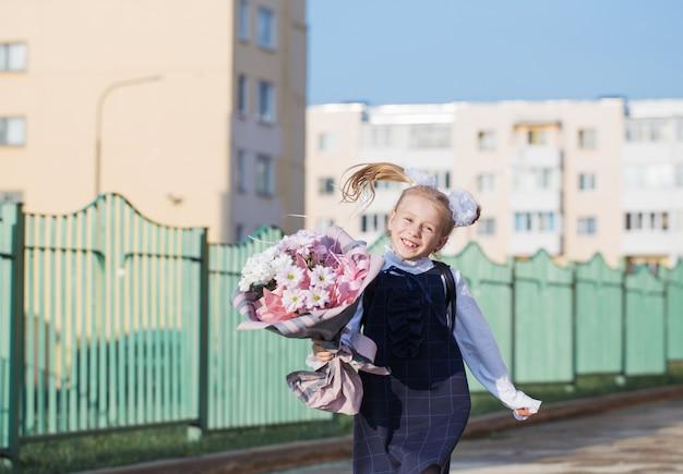 Petite écolière avec bouquet aller à l'école en journée ensoleillée