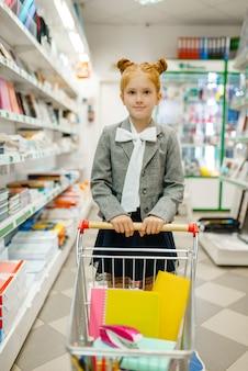 Petite écolière avec un chariot sur l'étagère en papeterie