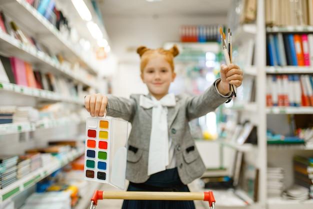 Petite écolière avec chariot, peintures à l'aquarelle et pinceaux, shopping dans une papeterie