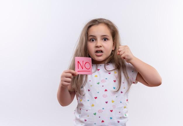 Petite écolière en colère portant un t-shirt blanc tenant une marque de papier sur un mur blanc isolé