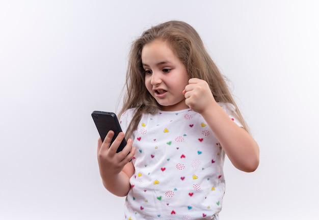 Petite écolière en colère portant un t-shirt blanc tenant le poing levé de téléphone sur un mur blanc isolé