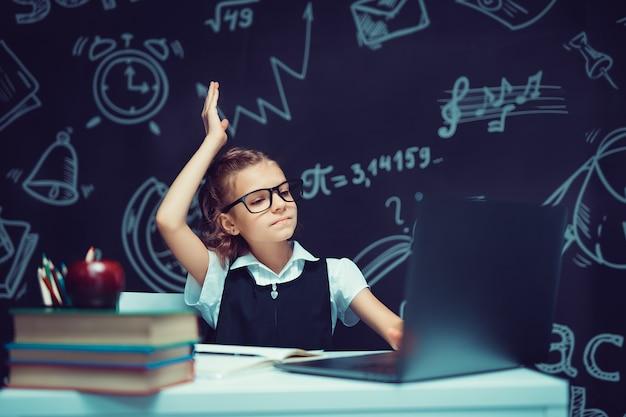 Petite écolière dans des verres étudiant avec fond de tableau noir école informatique retour à l'école