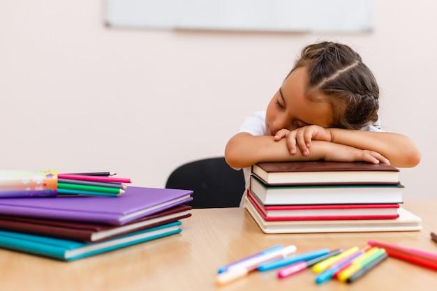 Petite écolière dormir dans une salle de classe près du tableau noir