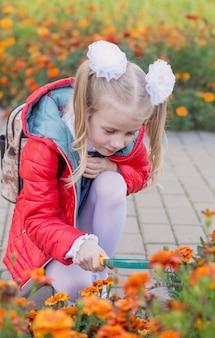 Une petite écolière examine des fleurs sur un parterre de fleurs à travers une loupe