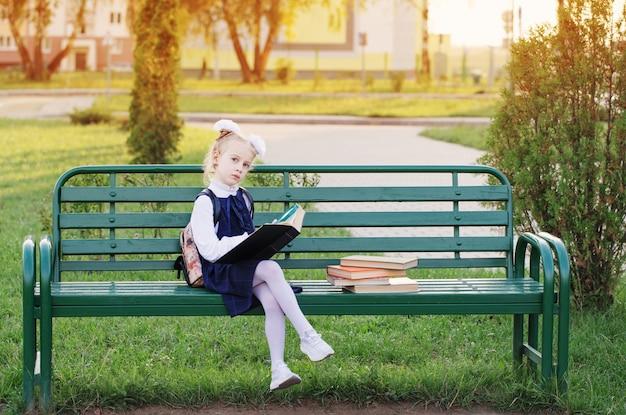 Petite écolière avec des livres assis sur un banc