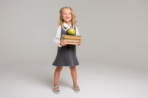 Petite écolière avec des livres sur un fond clair