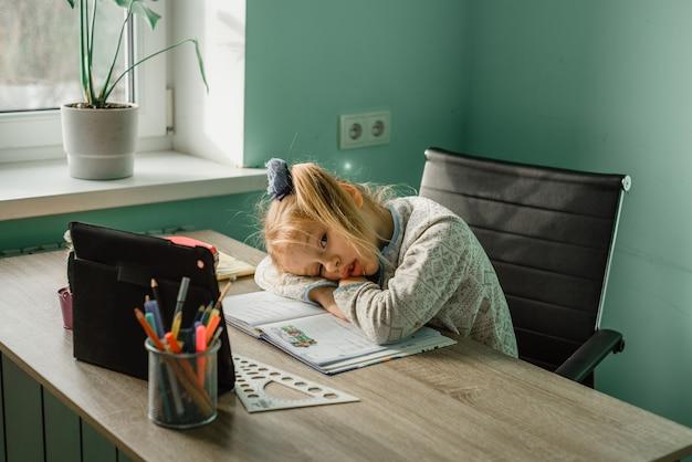 Une petite écolière à lunettes en a assez de la leçon en ligne à la maison