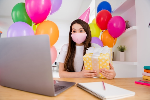Petite écolière en masque médical rose fête son anniversaire à l'intérieur