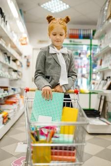 Une petite écolière met un cahier dans le chariot sur l'étagère de la papeterie