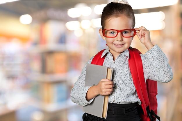 Petite écolière mignonne dans des verres sur le fond de bibliothèque