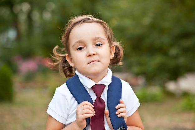 Petite écolière mignonne en uniforme avec sac à dos cartable.
