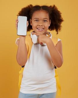 Petite écolière montrant un téléphone mobile vide