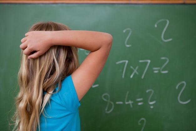 Petite écolière pensant en grattant le dos de sa tête
