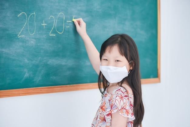 Petite écolière portant un masque fcial écrit réponse sur tableau noir en classe