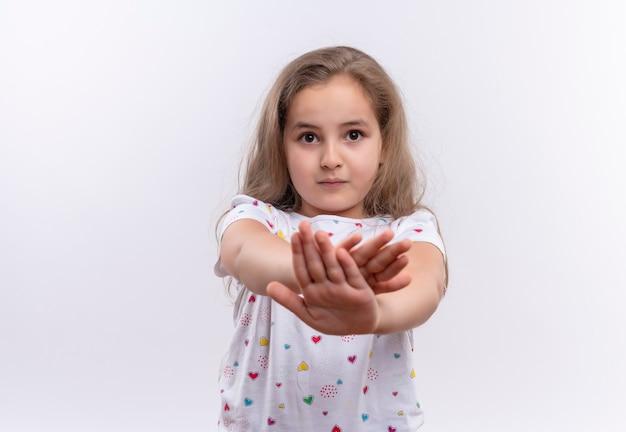 Petite écolière portant un t-shirt blanc montrant le geste d'arrêt sur un mur blanc isolé