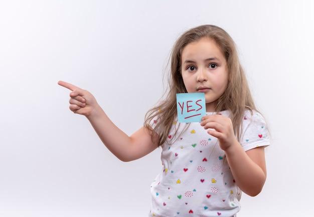 Petite écolière portant un t-shirt blanc tenant une marque de papier pointe vers le côté sur un mur blanc isolé