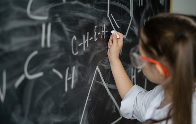 Petite écolière près du tableau résout un problème de chimie blouse blanche et lunettes hors ligne...