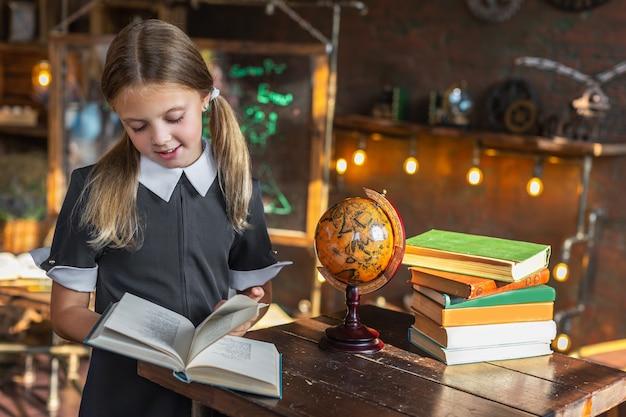 Une petite écolière regarde un livre tout en se préparant pour l'école, debout à une table avec des livres et un globe. retour à l'école. jeune écolière va acquérir des connaissances.